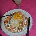 Chilaquilles with a fried egg on top. Layers of tortilla chips, chicken, tomato sauce, cheese, and cream, with lots of onions..