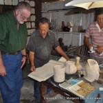 Alfredo Gonzales shows Philip some of the books he uses to reproduce ancient carvings.