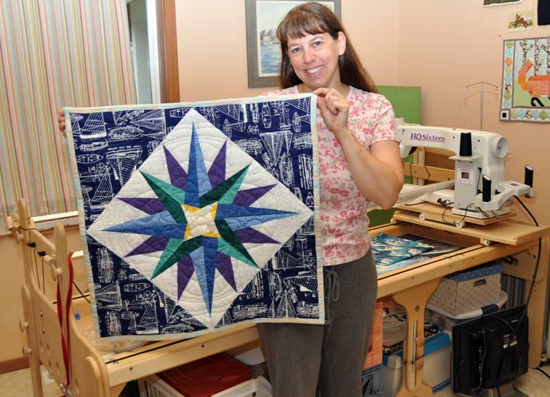 Karen with the compass rose side of the quilt