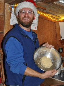 Barry shows off the dough in the bowl. It was cold enough to wear our Santa hats inside the boat.