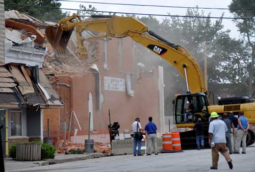 Construction equipment and workers tearing down a building