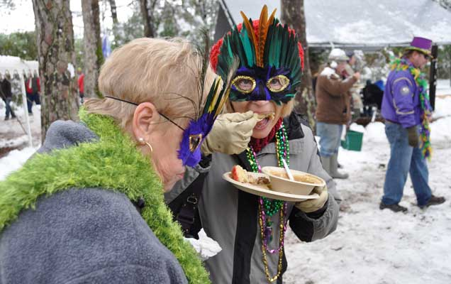 Two masked ladies caught in the unladylike act of eating gumbo