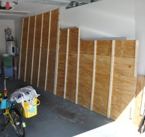 Plywood lofting floor leaning against the wall of the garage