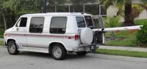 White van with 8 feet of aoluminum pipe sticking out the back