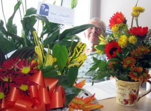 Dad in the hospital, surrounded by flowers from well-wishers