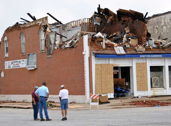 Men standing in the street beside Hometown Hardware, which was destroyed by tornado
