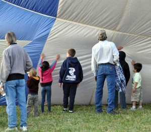 The kids watch a balloon being inflated