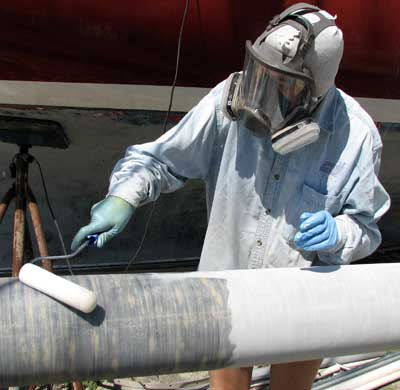 Meps applying epoxy with a roller to a mast