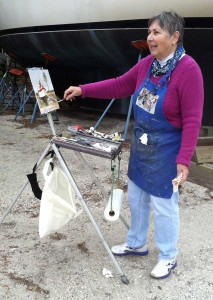 Artist working on her painting of a sailboat
