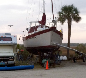 Average-looking fiberglass sailboat with lots of junk around it