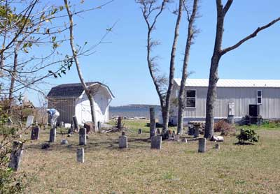 This cemetery is in the front yard of someone's single-wide mobile home